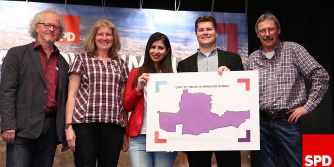 Gruppenbild mit fünf Personen auf einer Bühne, die eine Karte vom Ratswahlbereich Bothfeld-Vahrenheide halten