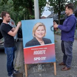 Zwei Männer stellen ein Plakat, auf der die SPD-Regionskandidatin Regina Hogrefe abgebildet ist, an einer Laterne auf.