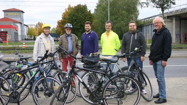 Sechs Personen mit Fahrrädern im Vordergund stehen an einer Straße